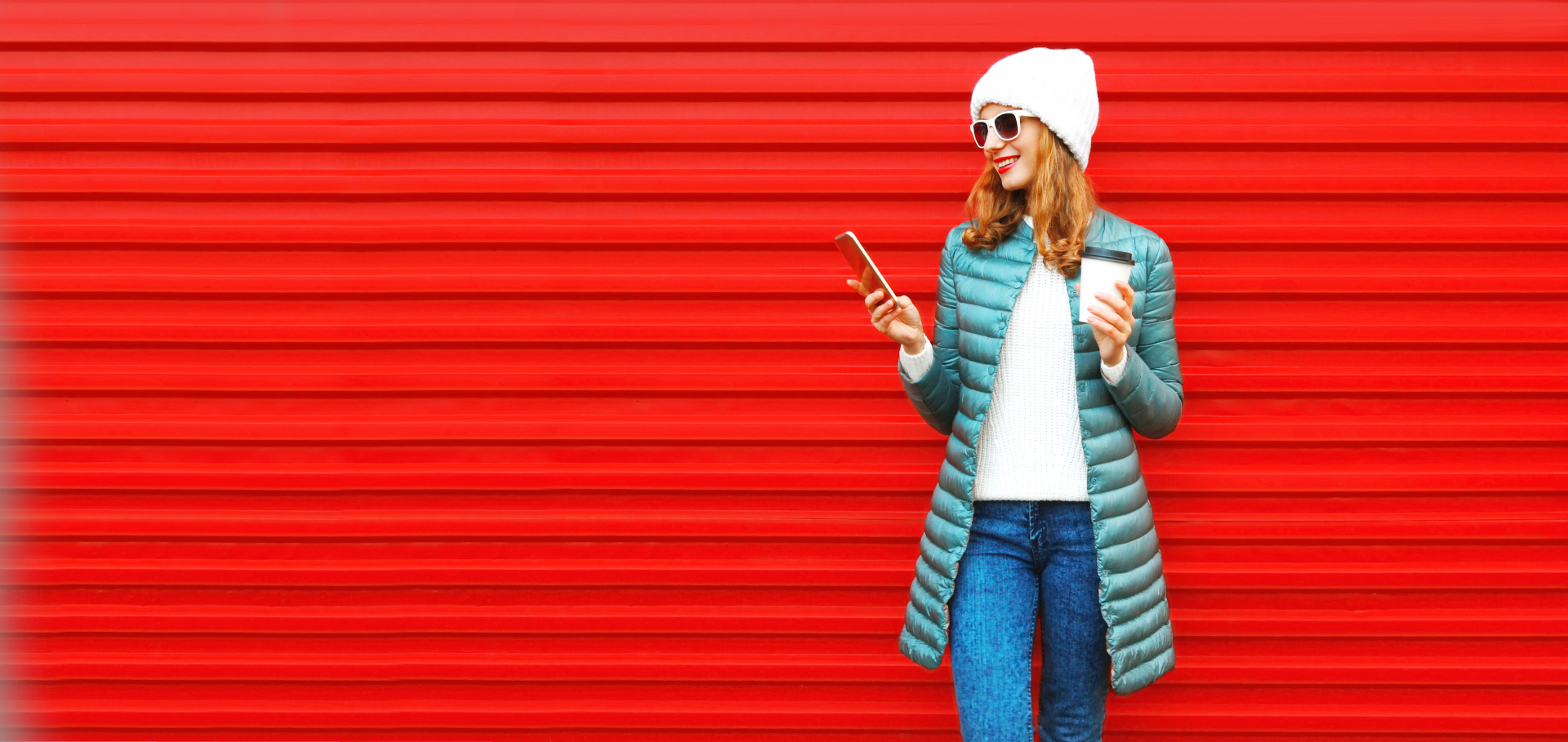 Fashion autumn smiling woman using smartphone holds coffee cup on a red background in the city